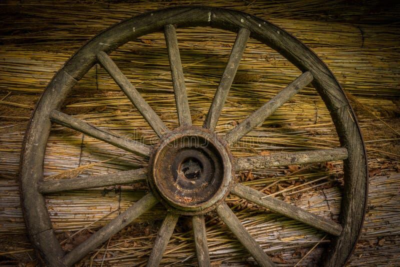 Wagenrad an der alten sraw Wand eines Hauses stockfotografie