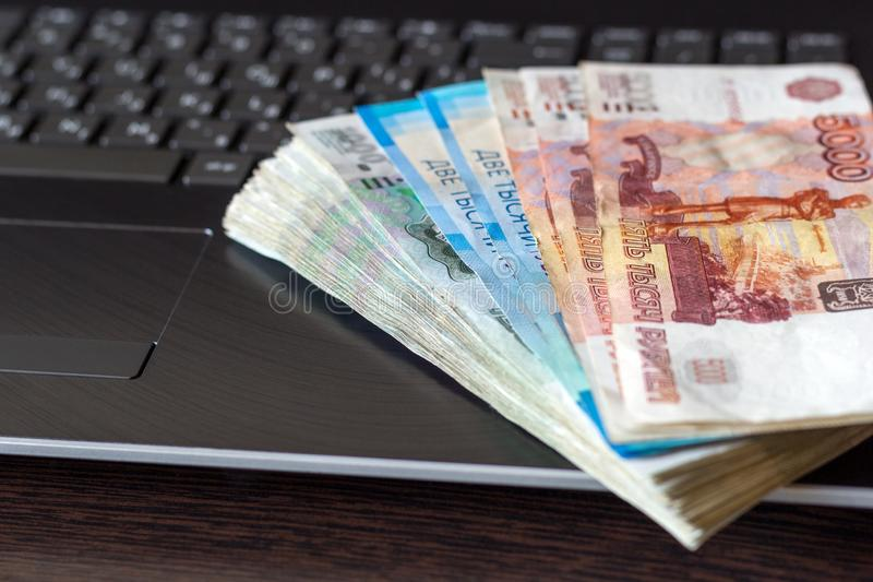 Wages in Russia. Russian paper currency lay on laptop keyboard folded like a fan. Different denominations banknotes. Payment fro freelance work concept. Close stock photos