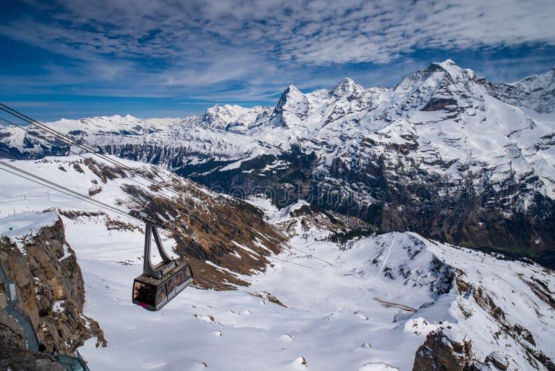 Wagon kolei linowej przeciw breathtaking panoramicznemu widokowi s?awni szczyty Eiger, Monch i Jungfrau w Szwajcarskich Alps, Szw fotografia stock