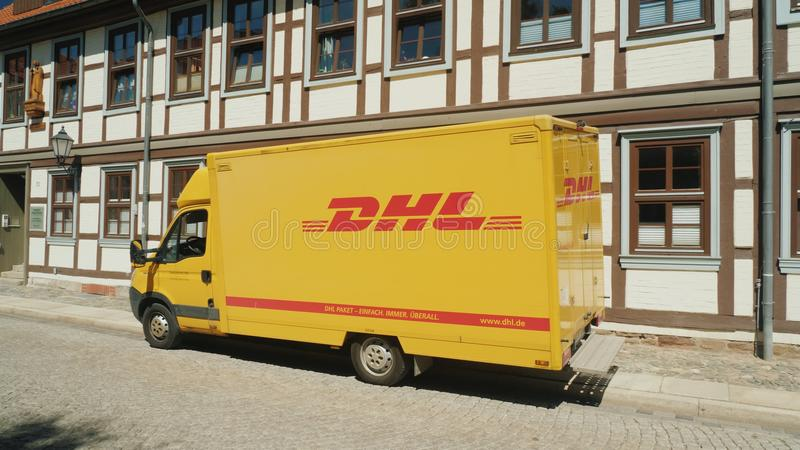 Wernigerode, Germany, May 2018: The wagon of the postal service DHL stands on a quiet street in a German town on the royalty free stock image