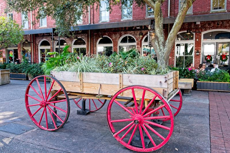 A Wagon wheel Cart sits outside filled with flowers stock photo