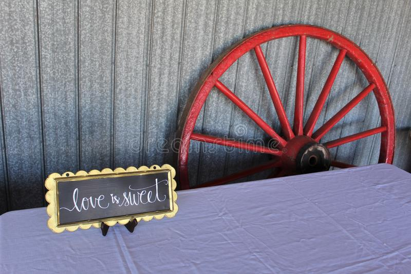A wagon wheel leaning against the wall of a barn with a sign on a table for a traditional old-fashioned wedding celebration. Decoration for a wedding celebration stock image