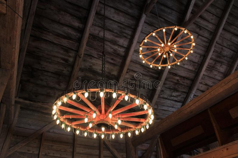Wagon wheels hung from the ceiling of a barn with lights for a traditional old-fashioned wedding celebration stock photos