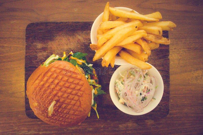 Wagyu hamburgare, bacon, cheddar, tryffel mayo, boisbourdonsås, knipor, gul senap, caramalised lökmesclun i en brioche arkivbild