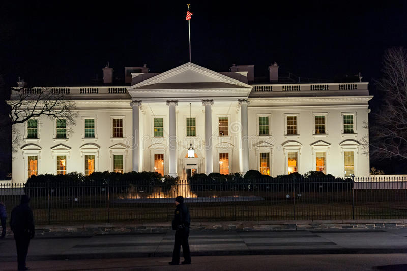 WAHINGTON, D.C. - JANUARY 09, 2014: White House at night. With Police Officer in foreground. royalty free stock photography