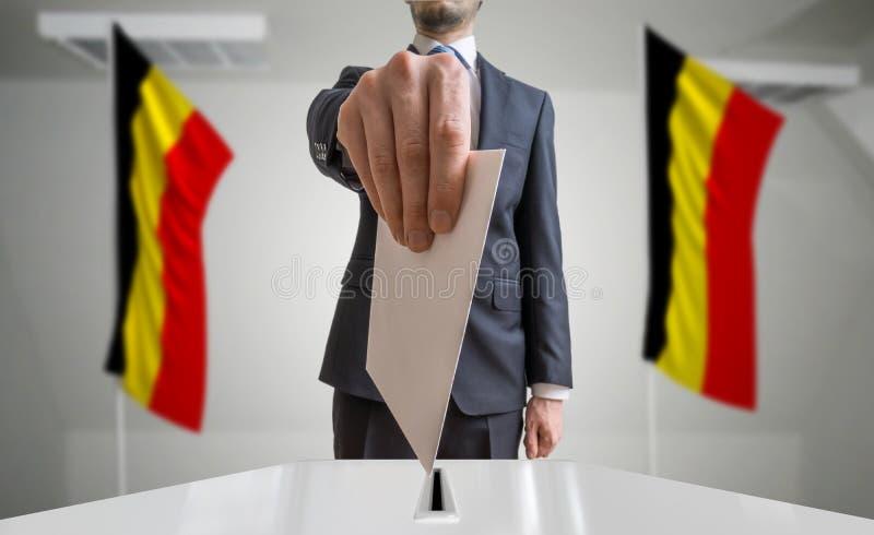 Wahl oder Referendum in Belgien Wähler hält Umschlag in der Hand über Stimmzettel Belgische Flaggen im Hintergrund lizenzfreie stockfotografie