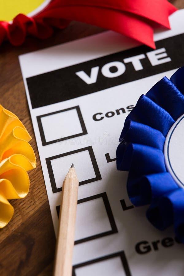 Wahl-Stimmzettel mit Rosetten von politischen Parteien stockfotografie
