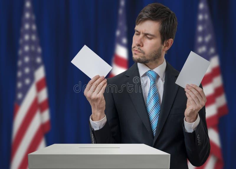 Wahl in USA Unentschlossener Wähler hält Umschläge in den Händen über Abstimmungsstimmzettel stockfotografie