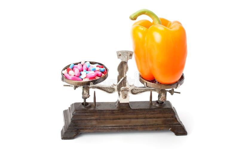 Wahl zwischen zwei Quellen von Vitaminen - Pillen oder gesundes Lebensmittel stockbilder