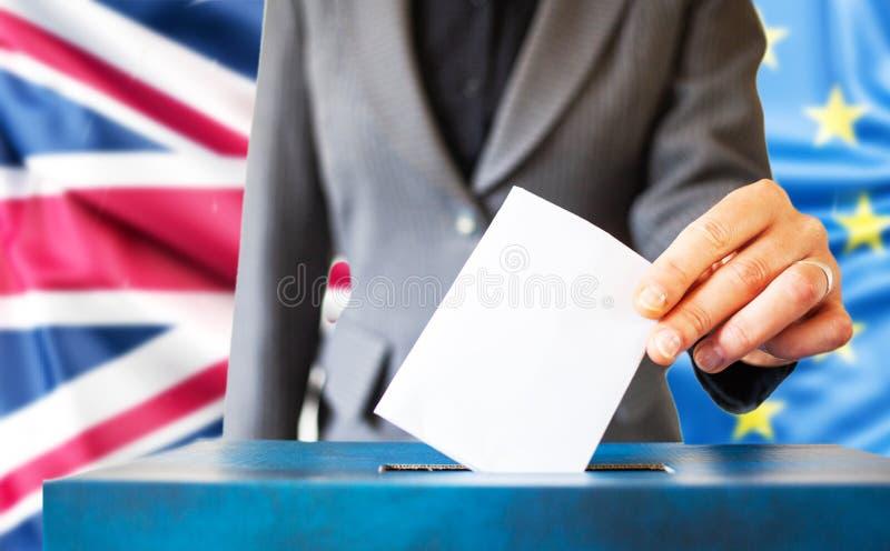Wahlen in der Europäischen Union Die Hand der Frau, die ihre Stimme in die Wahlurne setzt EU-Flagge im Hintergrund stockfotografie
