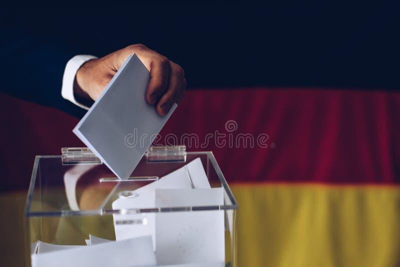 Wahlen in Deutschland Mann, der seine Abstimmung in die Wahlurne wirft stockfoto