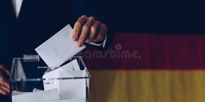 Wahlen in Deutschland Mann, der seine Abstimmung in die Wahlurne wirft lizenzfreies stockfoto