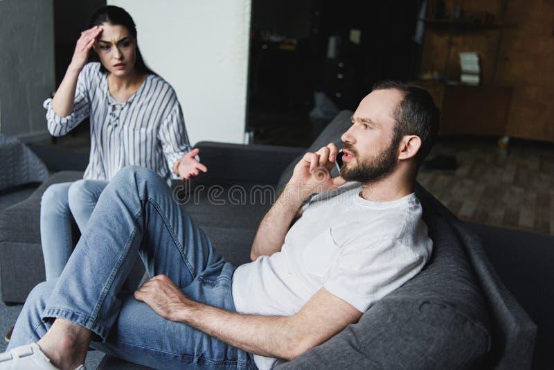 Wahnsinnige, die mit ihrem Ehemann während er telefonisch sprechend sprechen stockfotos