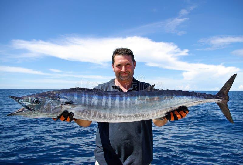 Wahoo fish. Lucky fisherman holding a beautiful wahoo fish royalty free stock images
