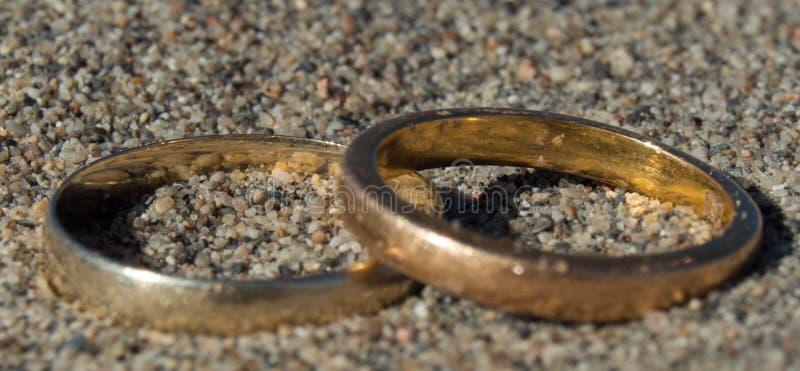 Wahre Liebhaber-goldene Paare Ringe in der Wüste stockbilder