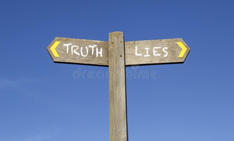 Wahrheit und Lügen - Begriffswegweiser mit einem Hintergrund des blauen Himmels stockfotos