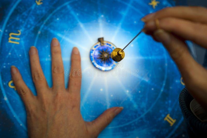 Wahrsager mit magischem Pendel auf blauem Horoskop wie Astrologie, Tierkreis geheimes Thema stockfotos