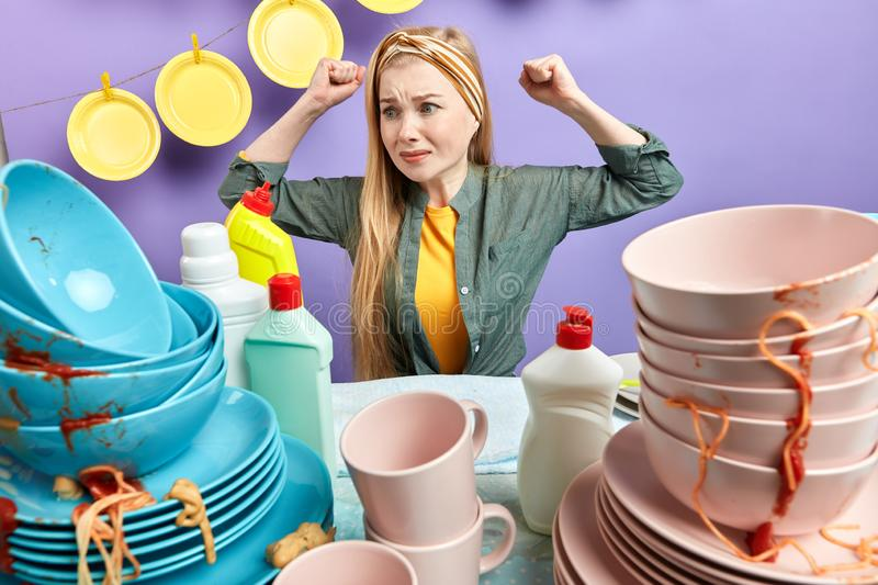 Waht dirty plates.upset caucasian woman looks with dissatisfcation at messy table royalty free stock photos