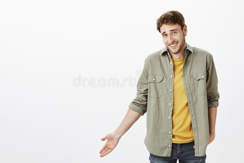So waht. Portrait of careless handsome bearded guy with curly hair, gesturing with palm and shrugging, laughing while. Hearing nonsense or funny story, standing stock image