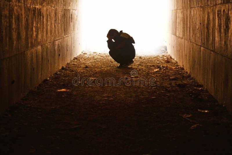 Waif zitting in de tunnel in verdriet stock afbeeldingen