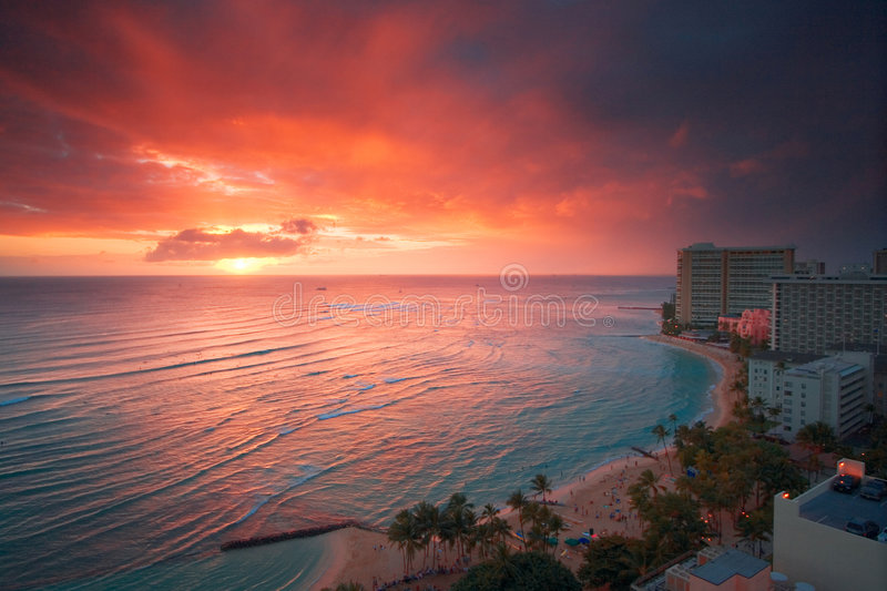 Waikiki resort sunset. Spectacular glowing sunset over turquoise blue water surrounded by high rise resort hotels with surfers from view of Waikiki Beach in stock photography