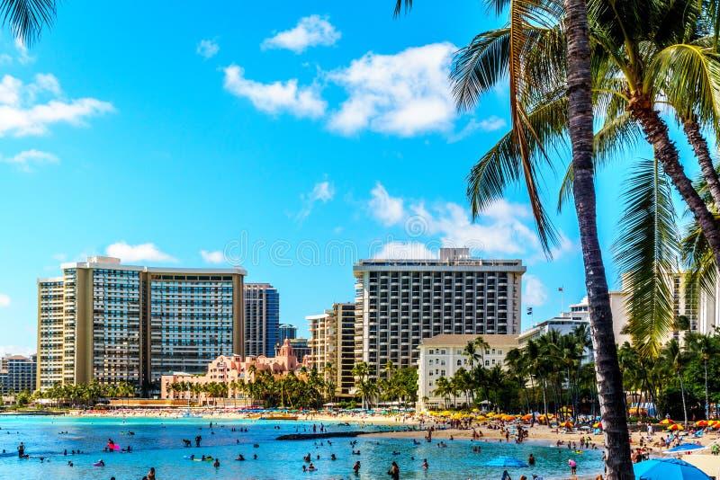 Waikiki strand, med dess många semesterorter under blå himmel och vitsand arkivbilder