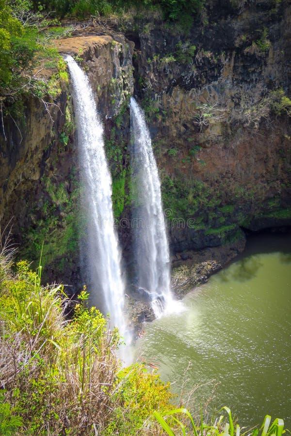 Wailua Falls, twin waterfalls flowing down in a green creek, Kauai, Hawaii, USA. Wailua Falls, twin waterfalls in a nice natural setting, Kauai, Hawaii, United royalty free stock photo