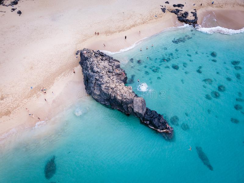 Waimea Beach Rock and Cliff Divers. Aerial view of rocky seascape at Waimea Bay Beach Park with divers jumping off cliff into clear turquoise water. Oahu, Hawaii royalty free stock image