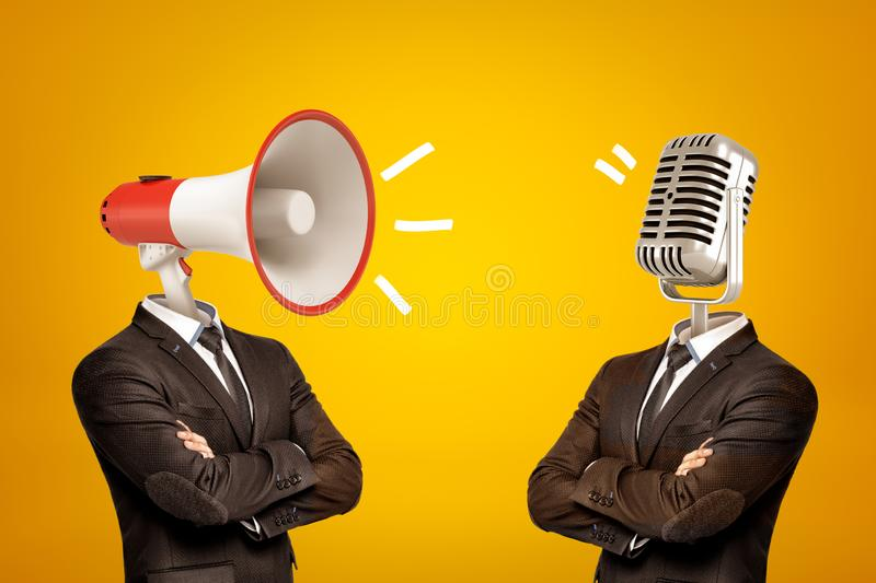 Waist-deep view of two businessmen standing in half-turn, arms folded, with megaphone and microphone instead of heads. stock photos