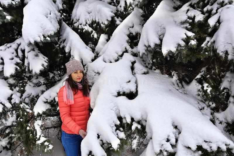 Waist shot of a happy and stylish beautiful woman in a bright coral jacket and blue jeans, smiling near a big snowy Christmas tree stock photos