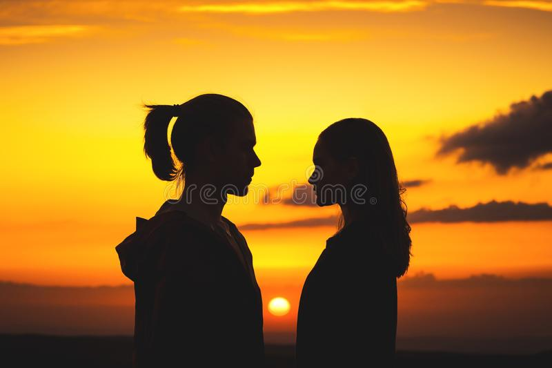 Waist silhouettes of a young millenial couple in love with a man and a girl look at each other. Two profile of a young stock photography