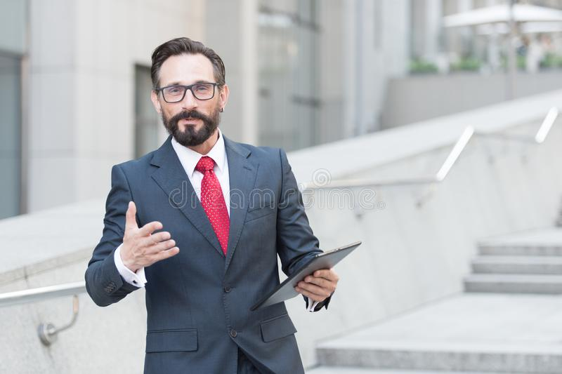 Waist up of affluent businessman having a talk with you while holding a tablet in hand stock photo