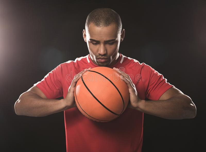 Young athletic man concentrating on orange ball stock images
