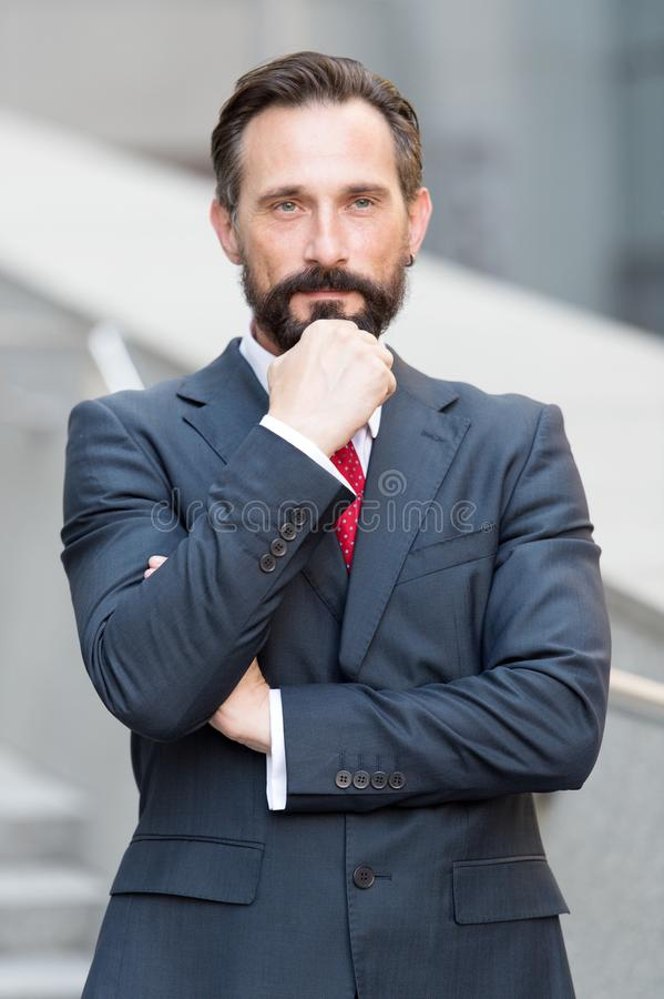 Waist up of calm man touching his beard and looking at you. Confident attractive elegant lawyer standing outdoors and looking into the distance while royalty free stock image
