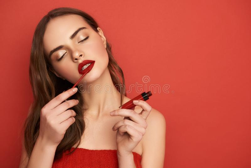 Portrait of attractive girl with closed eyes applying lips on red background stock photography