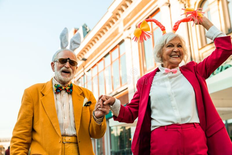 Smiling senior couple holding hands in the city stock images