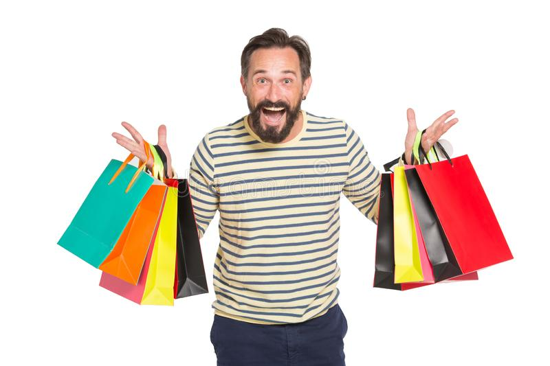 Waist up of delighted shopaholic holding paper shopping bags with purchases. Mature bearded man expressing excitement while holding paper bags with purchases in royalty free stock image