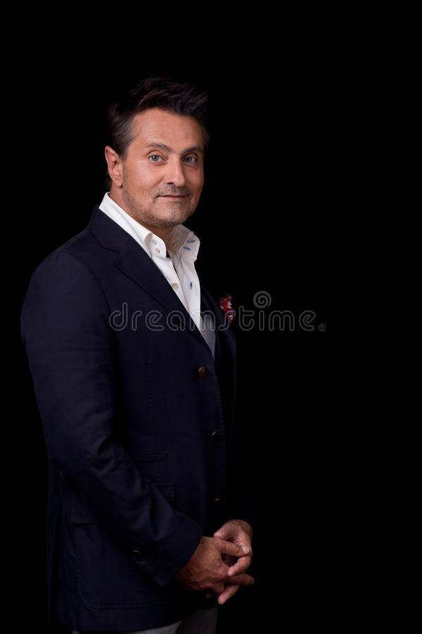 Waist up of the elegant man standing against the black background royalty free stock photo