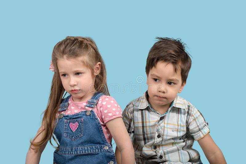 Close up emotional portrait of the smiling of the little angry. Waist up emotional portrait of the little girl and boy on blue background in studio. They have royalty free stock image