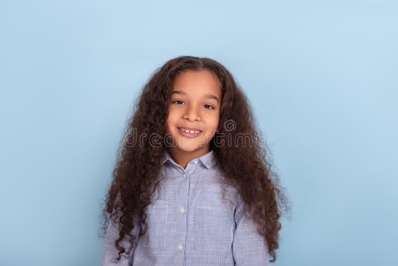 Waist up emotional portrait of mulatta frizzy girl wearing blue shirt against blue background in studio. Close up emotional portrait of mulatta frizzy girl royalty free stock image