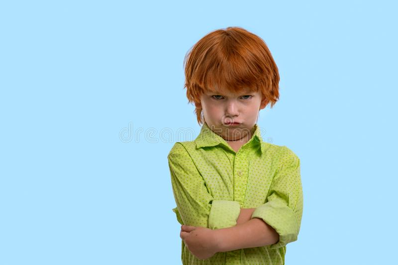 Waist up emotional portrait of redhead boy wearing green shirt on a blue background in the studio. Hi standing arms crossed and royalty free stock photo