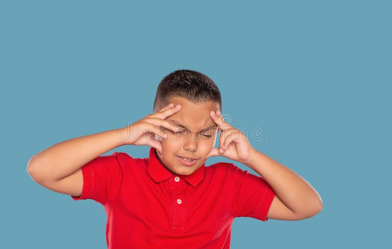 Half length   emotional portrait of a young boy experiencing stress and holding his head in frustration, isolated on blue. Waist up   emotional portrait of a stock photo