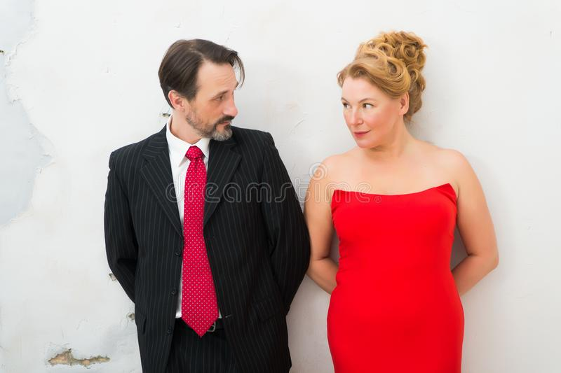 Waist up of enamored elegant couple looking at each other with love stock photography