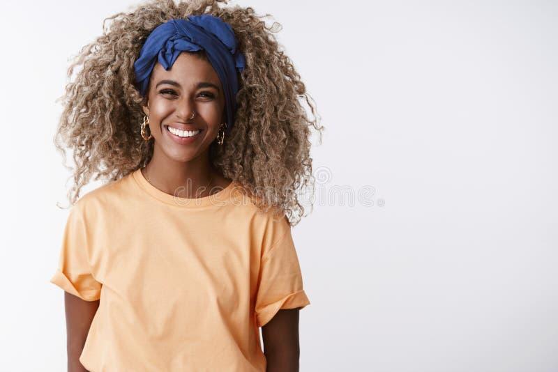Waist-up-erschossfreundliches und aufrichtiges, attraktives afrikanisch-amerikanisches blond-Girl mit afro-Frisur, stilvollem Hea lizenzfreies stockfoto