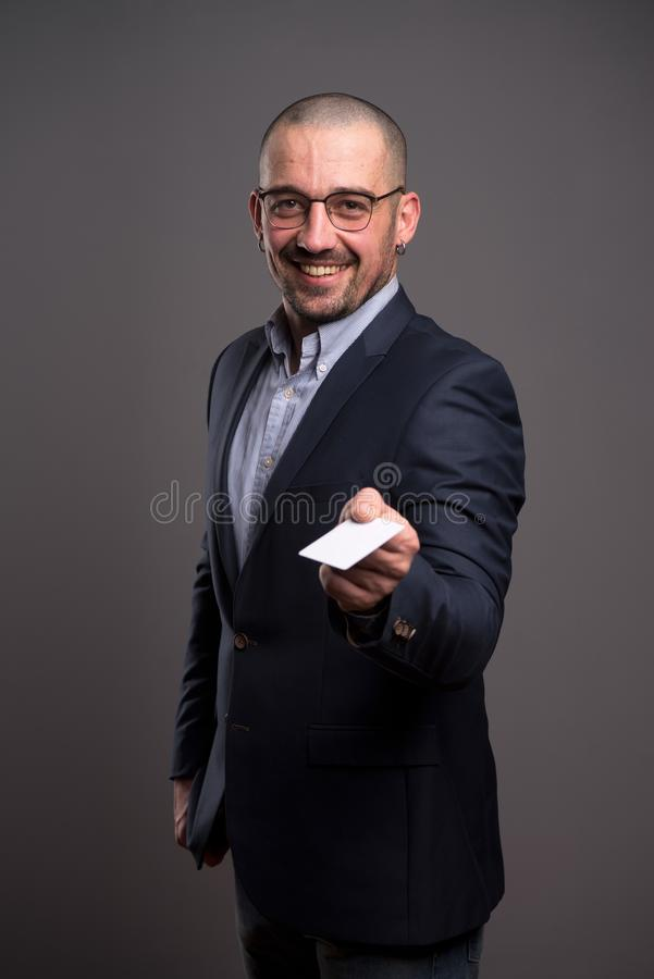 Waist up of excited businessman giving a credit card to you stock photography