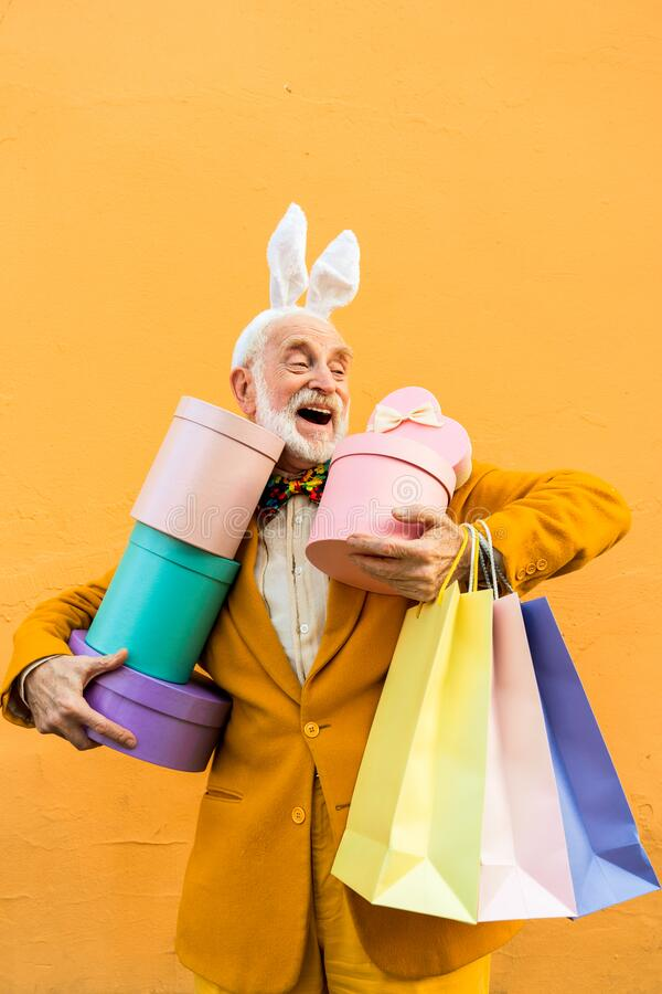 Funny elderly man is holding gifts in hands royalty free stock images