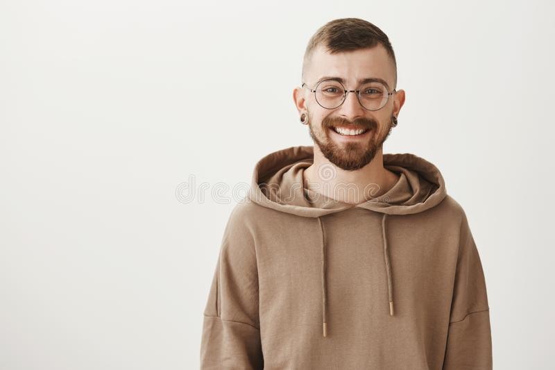Waist-up indoor shot of friendly handsome hipster guy with trendy haircut and glasses smiling cheerfully while standing stock photography