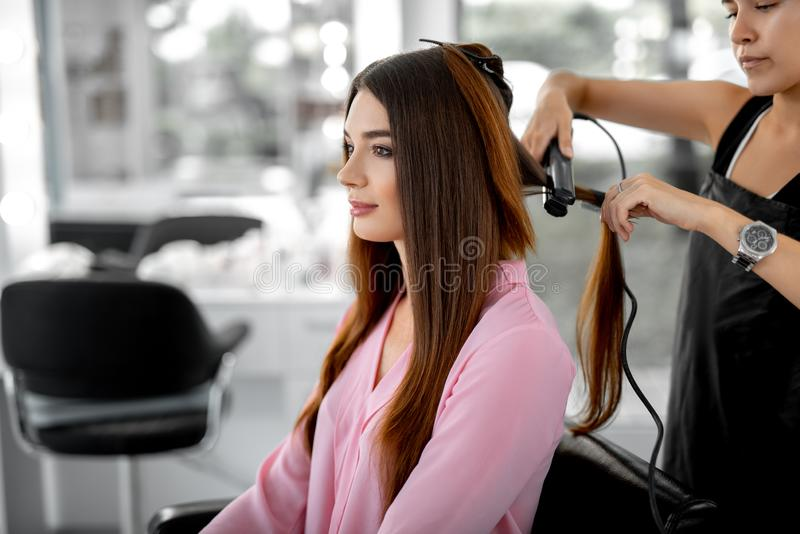 Beautiful lady is sitting inarmchair in beauty zone. Waist up photo of attractive young women looking in the mirror while female hairdresser styling her hair stock photography