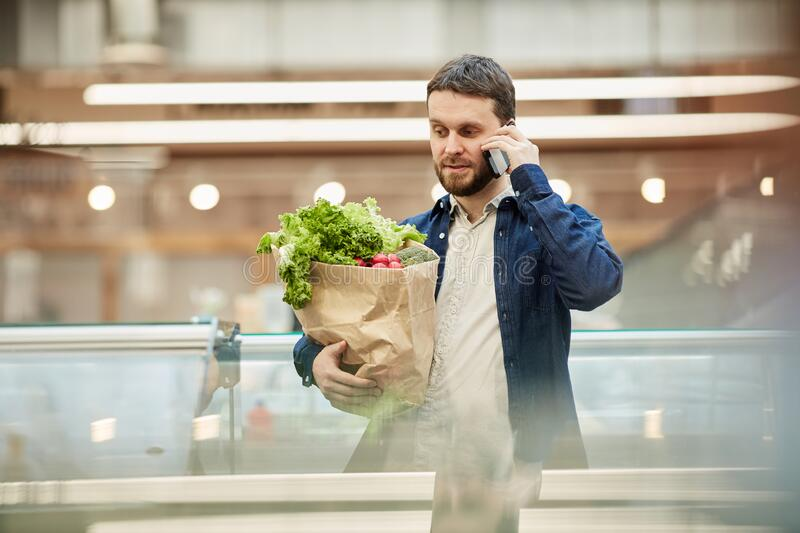 Adult Man Calling by Smartphone in Mall stock photo