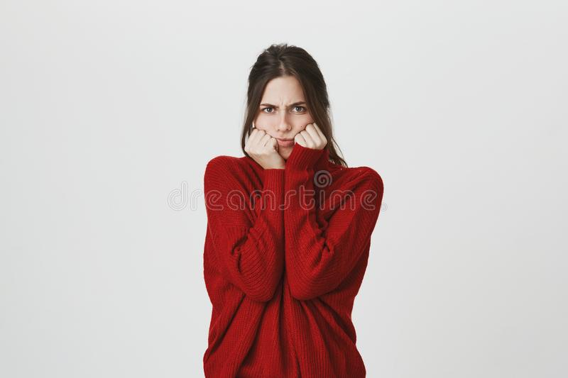 Waist-up portrait of angry young woman hiding her face, looks with furious and abused expression, frowns face in. Waist-up portrait of annoyed angry young woman stock image